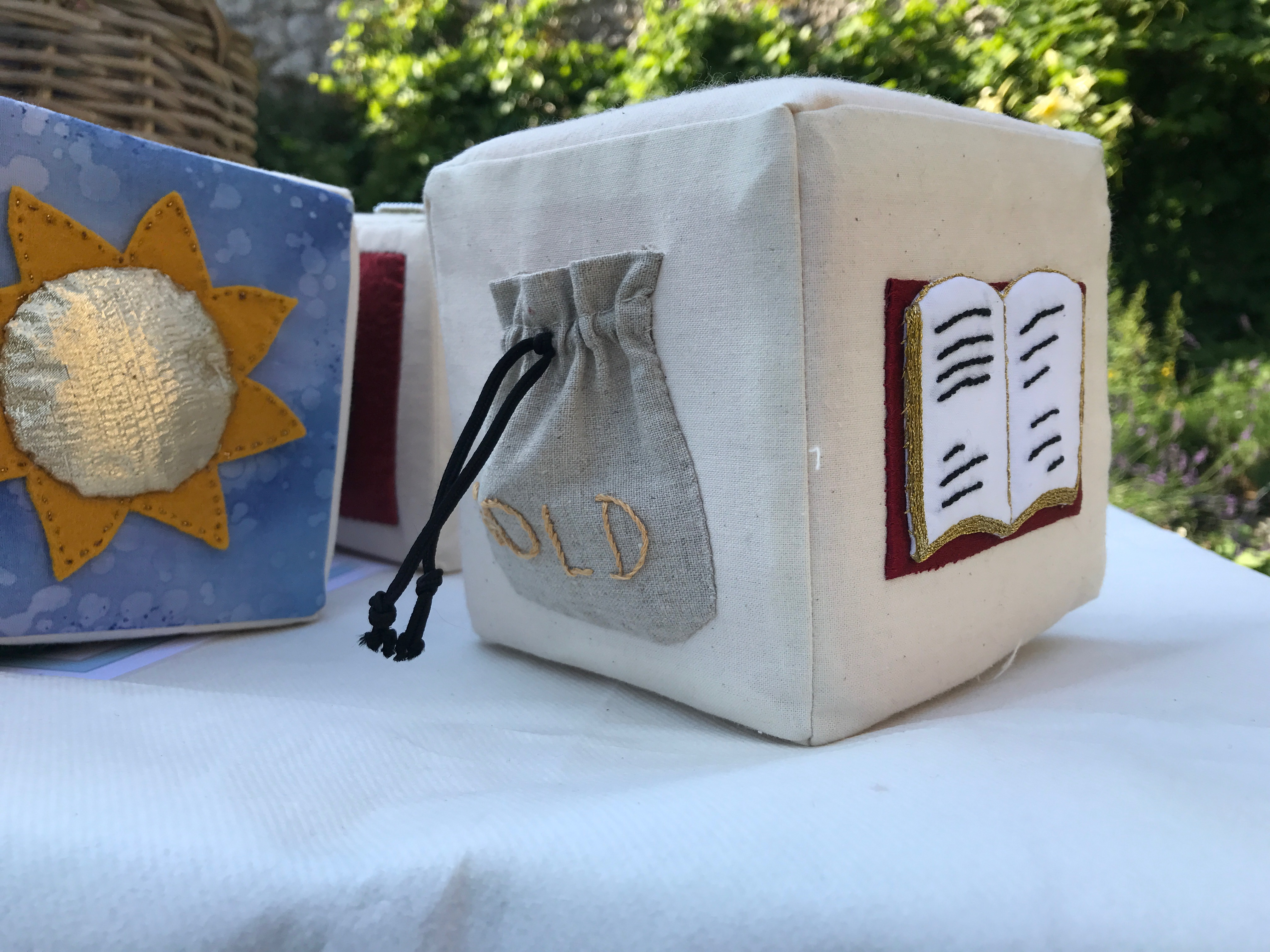 "Lewes Castle story cubes. Photograph of fabric-covered cubes. On each face of each cube is sewn a tactile representation for the different aspects of a story, for example a ""gold"" pouch and an open book on one cube, and a golden sun on another"